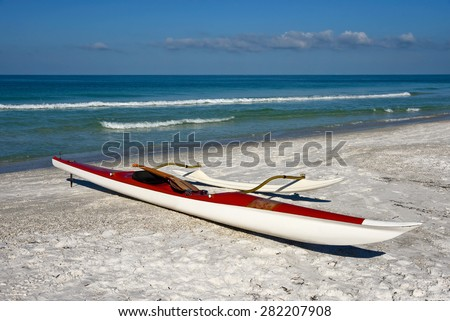 An outrigger canoe sitting on a white sandy beach with ocean in the background - stock photo