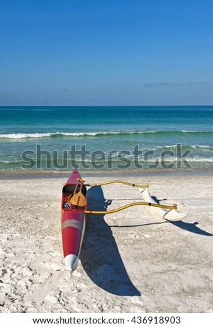 An outrigger canoe sitting on a white sandy beach with ocean in the background