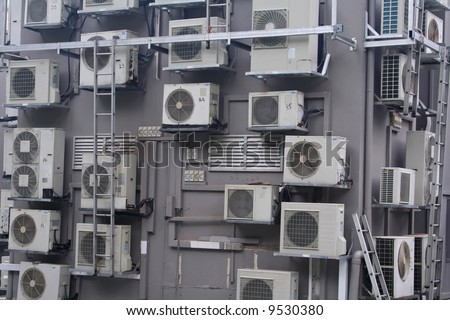 An over crowding of air conditioners on a building.