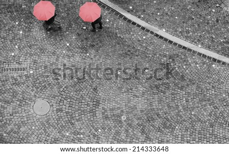 An overhead shot of a cobblestone street with two people hidden by their red umbrellas. Black and white image with the red umbrellas as the only color. - stock photo