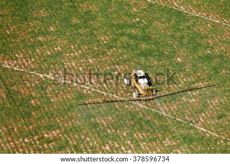 An overhead view of a crop duster spraying potato fields.  A weak sulfuric acid solution is sprayed to kill potato vines in preparation for harvest. - stock photo