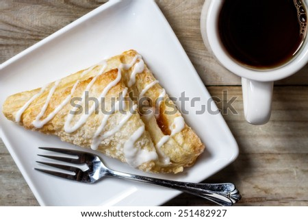 An overhead view of a frosted apple turnover and a cup of coffee