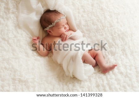 An overhead view of a sleeping 8 day old newborn baby girl wearing a rhinestone headband. She is wrapped in white gauzy fabric and sleeping on her back on white ruffled fabric.