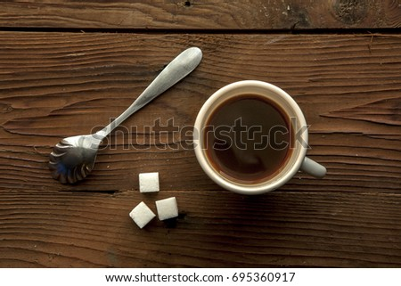 An overview of a cup of coffee, sugar cubes, and a spoon.