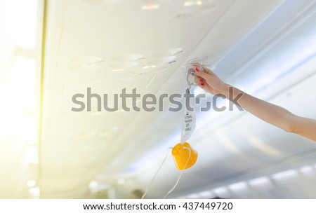 an oxygen mask on the plane.selective focus, Soft focus .hands,selective focus. - stock photo