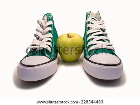 An pair of sneakers with an apple standing between with a white background
