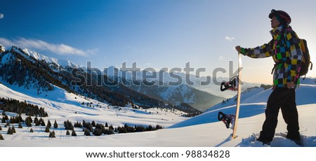 An panorama image with snowboarder with a helmet and glasses on the background of high snow-mountain Alps in Grindelwald, Swiss - stock photo