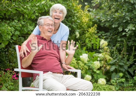 An romantic elderly couple sitting outside and having fun with each other looking into the camera