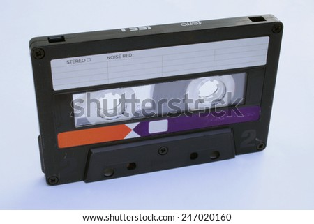An 1980s style tape audio cassette as it was sold in asian markets. Used condition with marks and scratches. In upright position on white background - stock photo