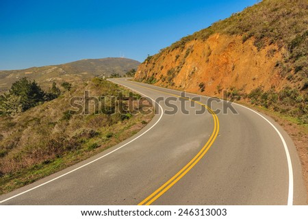 An S turn though the hills by a road with a double yellow line
