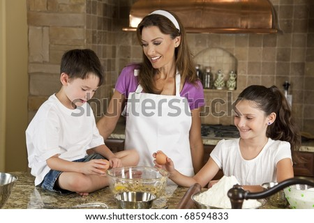 An smiling mother, daughter and son family cooking and baking chocolate chip cookies in a kitchen at home - stock photo