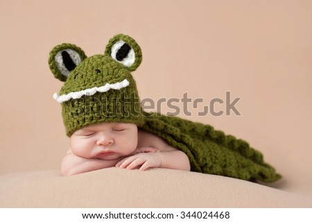 An two week old newborn baby boy wearing a green alligator costume. He is sleeping on a tan blanket. - stock photo