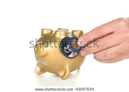 An unconscious piggy bank being examined with a stethoscope for its financial life after a poor economy and recession. - stock photo