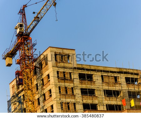 An under construction building with working crane at sunset in Hanoi, the capital of Vietnam. Its a dynamic and energetic city on the move. Urban development concept. Industrial Background.
