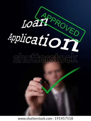 An underwriter writing Loan Application approved on a screen. - stock photo
