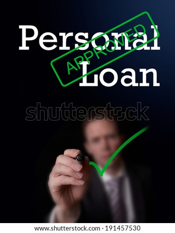 An underwriter writing Personal Loan approved on a screen. - stock photo