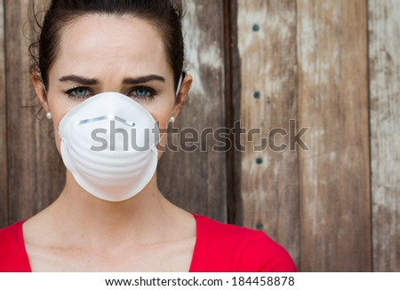 An unhappy woman wearing a face mask to deal with virus or pollution. - stock photo