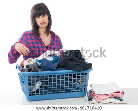 an unhappy young beautiful woman ironing clothes