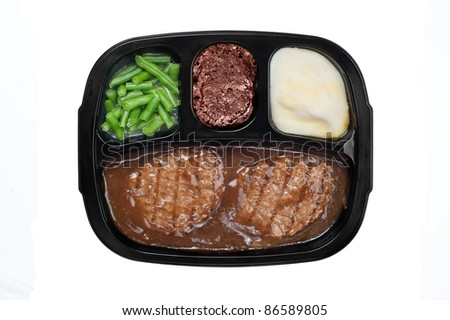 An unhealthy Salidbury steak TV dinner with gravy, mashed potatoes and a brownie dessert in a plastic tray isolated on white - stock photo