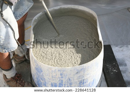 an unidentifiable contractor mixes stucco in a blue plastic drum in preparation of applying it to a home remodel project. stucco is an important part of home remodeling and is very useful  - stock photo