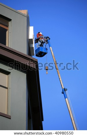 "an unidentifiable man in a ""man lift"" or crain working on a building sign - stock photo"