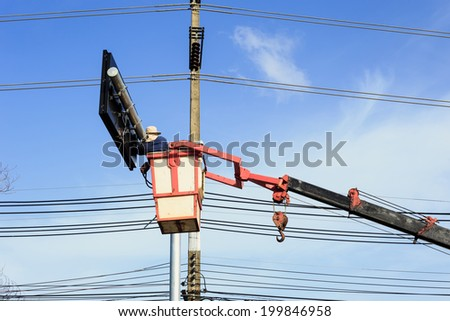 "an unidentifiable man in a ""man lift"" or crain working on a traffic sign - stock photo"