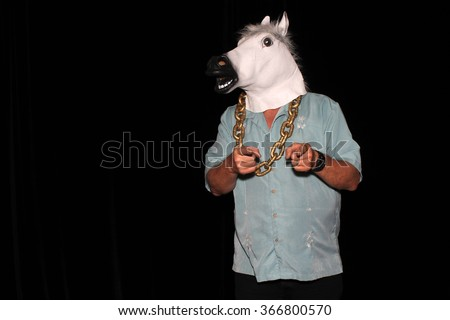 An unidentifiable man wears a White Rubber Horse Head Mask while wearing a Gold Chain and points to the camera in a Photo Booth. With Black velvet curtains and room for your text - stock photo