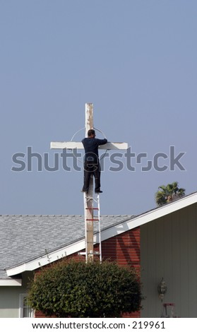an unidentifiable person painting a cross at a church