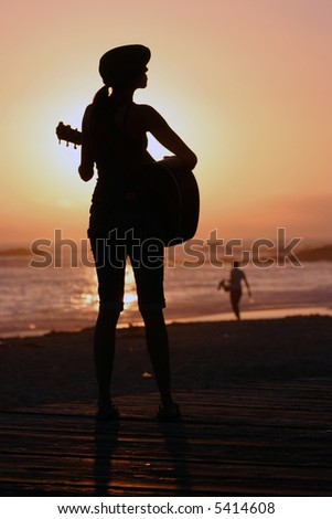 an unidentifiable young woman plays her guitar as the sun sets behind her in Laguna Beach California - stock photo