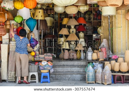 An unidentified woman is arranging handmade products in a shop. These products are made from bamboo and woven rattan on the sidewalk of Hang Trong street, Hanoi, Vietnam.