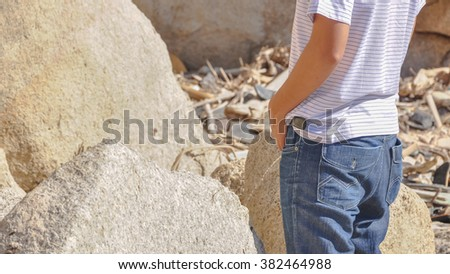 An unidentified young Asian man in casual dress is urinating in the rocks beach at natural bay. Urinating in public places is popular in Vietnam. Panoramic Style. - stock photo