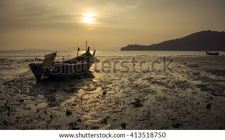 An unknown fisherman's boat by the beach during sunrise at Hammers Bay,  Penang,  Malaysia.