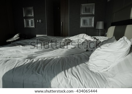 An unmade bed with pillows, sheets, and a blanket in the morning. - stock photo