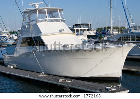 An unmarked, bright white yacht sits tied to the dock.  Perfect for someone to add their own text or graphics in the whitespace. - stock photo