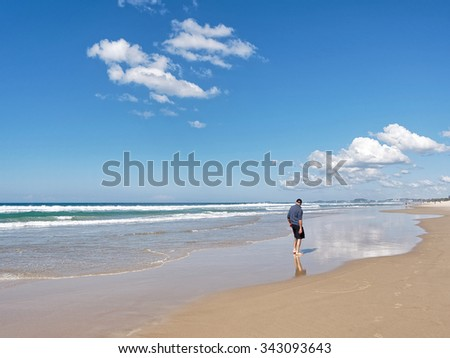 An unrecognizable bare feet man watching the waves with his back to camera.