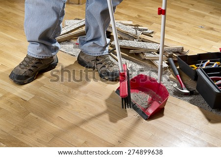 An unrecognizable person with a broom sweeping floor into dustpan. - stock photo