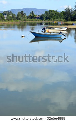 An unrecognized fisherman in a lonely wooden fishing Boat on a calm blue sea - stock photo