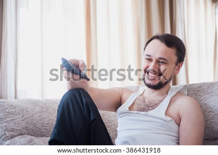 an unshaven man sits at home on the couch