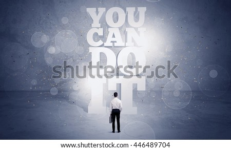 An unsure business person standing with his back in blue urban environment with big block letters saying you can do it concept - stock photo