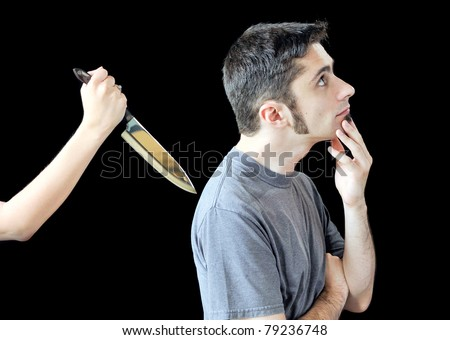 An unsuspecting young man getting stabbed in the back by a woman. - stock photo