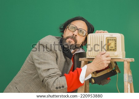 An untidy bizarre man, wearing big patched glasses and a toupee, listening to a station on an antique bakelite tube radio on a ladder, over green background