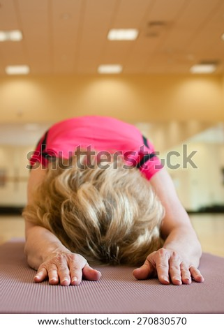 An unusual angle of an older woman resting her forehead on her yoga mat in child's pose.  The blond woman is wearing a bright pink shirt and she is practicing on a mauve colored yoga mat.   - stock photo