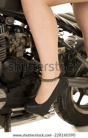 An up close picture of a woman's leg and heel on the motorcycle. - stock photo