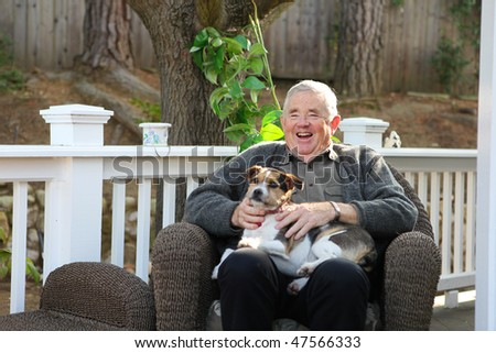 An upbeat joyful retired elderly man at home relaxing with dog - stock photo