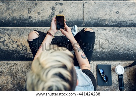 An upper view of stylish young woman using her cell phone while sitting on stairs in the city. We live in a connected world