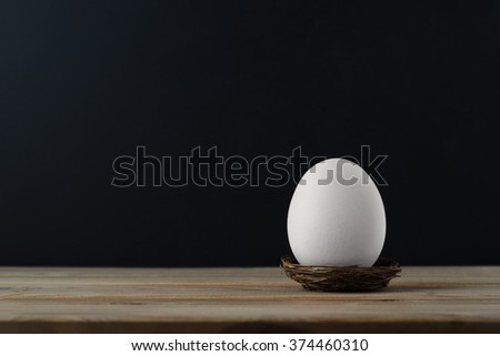 An upright chicken's egg (whitened) in small nest on wood plank table.  Black chalkboard background provides copy space. - stock photo