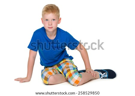 An upset boy in the blue shirt is sitting on the white background - stock photo