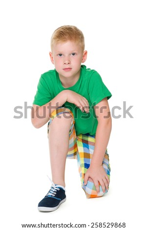 An upset boy in the green shirt is sitting on the white background