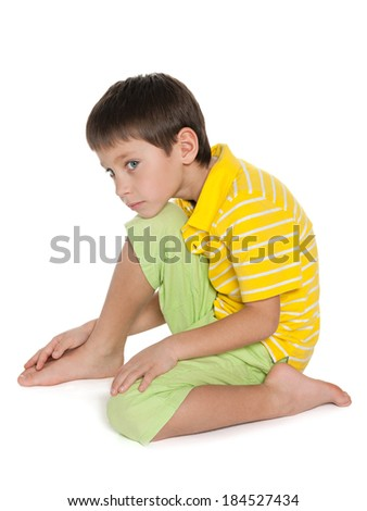 An upset boy in yellow shirt is sitting on the white background - stock photo