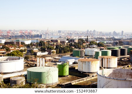 An urban industrial landscape with residences mass storage tanks harbour and city